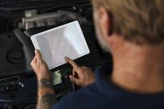 Propriétaire d'atelier de réparations automatiques vérifiant le concept de Tablette photos stock