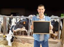 Propriétaire d'un ranch de bétail montrant le tableau noir Photo stock