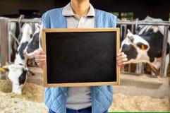 Propriétaire d'un ranch de bétail montrant le tableau noir Image stock