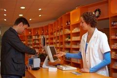 Propriétaire dans le paiement de pharmacie photos stock