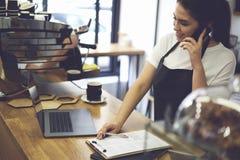 Propriétaire de café féminin tenant la machine proche de café à la barre avec l'ordinateur portable moderne Photo libre de droits