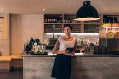 Propriétaire de café se tenant au compteur images stock