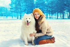 Propriétaire de sourire heureuse de femme et chien blanc de Samoyed en hiver Photographie stock libre de droits