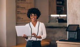 Propriétaire féminin de café avec l'ordinateur portable image libre de droits
