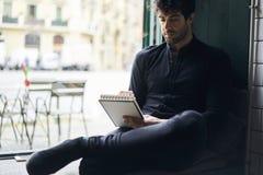 Propriétaire mûr des affaires dans une chemise noire se reposant dans l'espace coworking près de faire de la publicité le secteur Photo stock