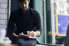 Propriétaire mûr des affaires dans une chemise noire se reposant sur la fenêtre dans l'espace de collègue Photo libre de droits