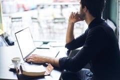 Propriétaire mûr des affaires dans une chemise noire utilisant la connexion gratuite dans le café Photos stock