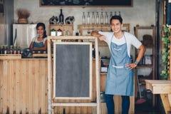 Propriétaire masculin asiatique de café avec le conseil vide photos stock