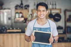 Propriétaire masculin asiatique de café avec le conseil vide photographie stock libre de droits