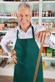 Propriétaire masculin avec le bâton se tenant dans le magasin Photo libre de droits