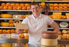 Propriétaire masculin beau d'un magasin de fromage se tenant avec le morceau de fromage Images libres de droits