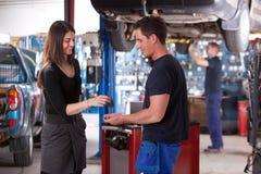 Propriétaire relâchant outre du véhicule au mécanicien Photo stock