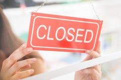 Propriétaire tenant le magasin d'habillement fermé de connexion Images stock