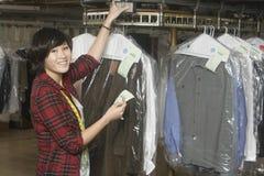 Propriétaire tenant le reçu par le rail de vêtements dans la blanchisserie image stock