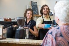 Propriétaires de café servant le café à la femme au compteur Image stock