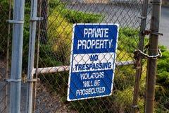 Propriedade privada azul nenhum sinal infrinjindo em uma cerca do elo de corrente Foto de Stock Royalty Free