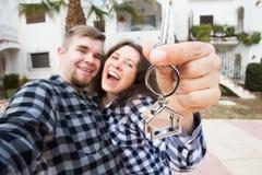 Proprietà, bene immobile e concetto di affitto - giovane mostra divertente felice delle coppie chiavi della loro nuova casa fotografia stock libera da diritti