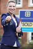 Proprietà residenziale dell'esterno diritto femminile di agente immobiliare che tiene chiave Immagine Stock