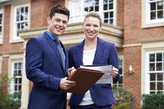 Proprietà residenziale dell'esterno diritto maschio e femminile di agente immobiliare immagini stock libere da diritti
