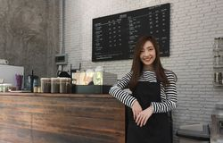 Proprietário da jovem mulher de um suporte do café na frente do contador do café, yo fotos de stock