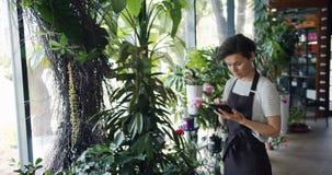 Proprietário da loja de flor que conta plantas e que usa a tabuleta para redigir para baixo a informação video estoque