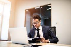 Proprietário empresarial especializado do homem vestido no terno oficial e vidros que leem da informação do livro de texto sobre  fotografia de stock