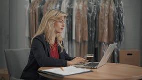Proprietário empresarial pequeno que trabalha com o portátil em seu escritório video estoque