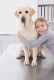 Proprietário louro que abraça seu cão bonito imagens de stock royalty free