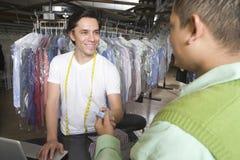 Proprietário que recebe o cartão de crédito do cliente na lavanderia foto de stock royalty free