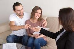 Proprietários bonitos dos pares que obtêm chaves dos bens imobiliários a Fotografia de Stock Royalty Free