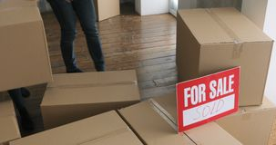 Proprietários de casa novos que desembalam caixas conceito movente do dia caixas de cartão grandes na casa nova filme