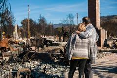 Proprietários, verificando a casa e a jarda queimadas e arruinadas após o fogo fotos de stock