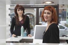 Proprietario con il cliente che acquista i prodotti per i capelli immagine stock