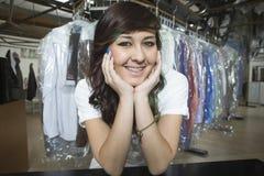Proprietario con la mano su Chin Leaning At Laundry Counter Fotografia Stock