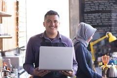 Proprietario del caffè al suo contatore della caffetteria facendo uso del computer portatile il suo partner che lavora in un fond immagini stock