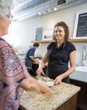 Proprietario del caffè che serve alimento dolce alla donna senior Immagini Stock Libere da Diritti