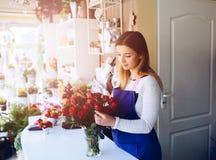 Proprietario della giovane donna del negozio di fiorista che prepara mazzo delle rose rosse Immagini Stock Libere da Diritti