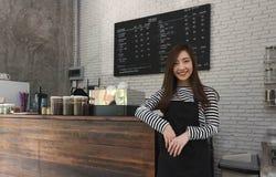 Proprietario della giovane donna di un supporto del caffè davanti al contatore del caffè, yo fotografie stock