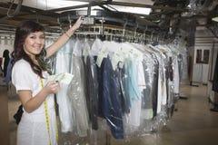 Proprietario della lavanderia con la ricevuta che controlla i vestiti fotografia stock libera da diritti