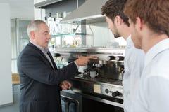 Proprietario di ristorante senior accanto al bar con i lavoratori Fotografia Stock