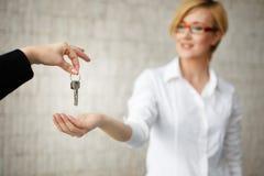 Proprietario felice che passa le chiavi dalla casa in ufficio Fotografia Stock