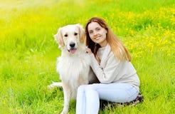 Proprietario felice e cane di golden retriever che si siede insieme Fotografia Stock