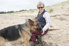 Proprietario femminile che dà ad alsaziano dell'animale domestico una bevanda di acqua un giorno soleggiato caldo Fotografie Stock