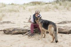 Proprietario femminile che dà ad alsaziano dell'animale domestico una bevanda di acqua un giorno soleggiato caldo Fotografia Stock
