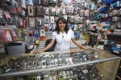 Proprietario femminile che sta nel negozio mobile Immagine Stock