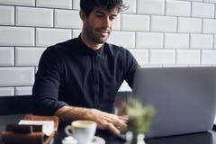 Proprietario maturo di un affare in una camicia nera che si siede al computer che si collega al collegamento senza fili 4G Fotografia Stock