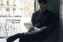 Proprietario maturo di un affare in una camicia nera che si siede nello spazio coworking vicino ad annunciare area Fotografia Stock