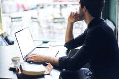 Proprietario maturo di un affare in una camicia nera facendo uso di collegamento libero in caffetteria Fotografie Stock