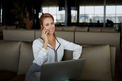 Proprietario sorridente della donna che parla sul telefono cellulare con il cliente mentre sedendosi con il computer portatile ne Fotografie Stock