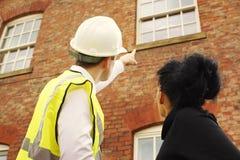 Propriétaire d'une maison de constructeur d'arpenteur regardant la propriété Images stock